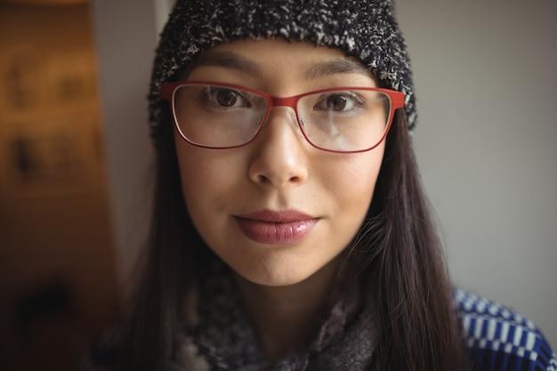 Retrato de mulher usando boné e óculos em um café