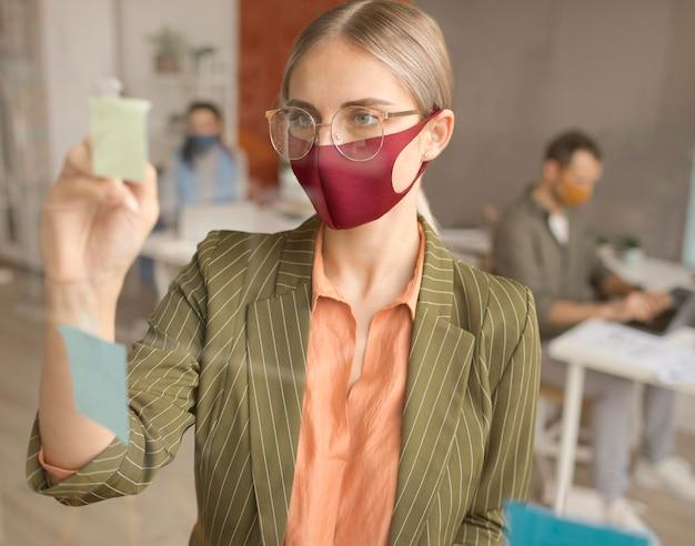 Retrato de mulher usando máscara no trabalho