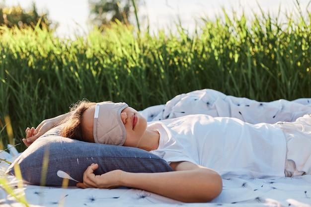 Retrato de mulher usando máscara para dormir e camiseta branca, deitada em uma cama macia no meio de um campo verde ou prado, a mulher dorme ao ar livre no verão.