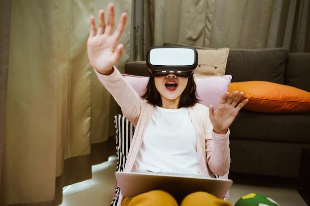 Retrato de mulher usando óculos de realidade virtual com emocionante em casa