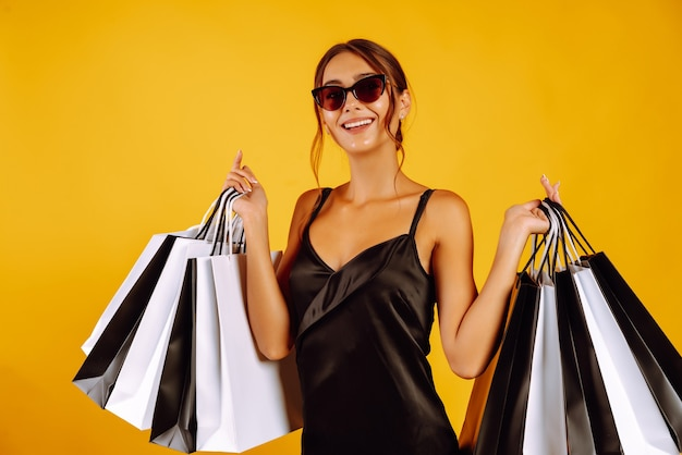 Retrato de mulher usando óculos escuros e segurando sacolas de compras