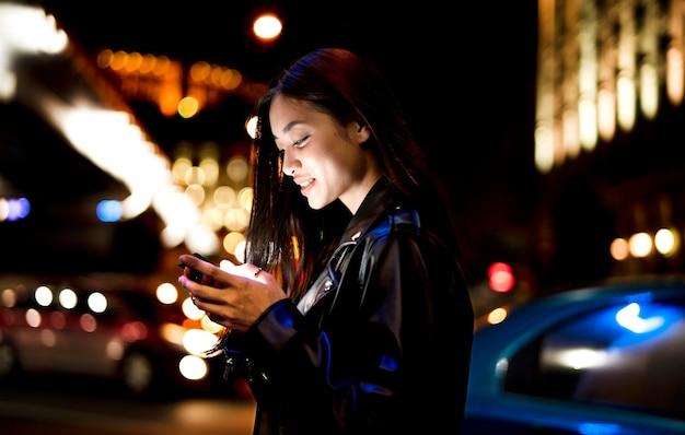 Retrato de mulher usando smartphone à noite nas luzes da cidade