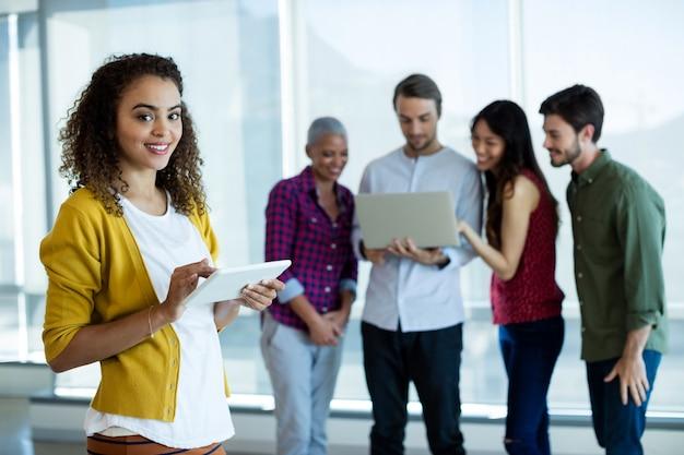 Retrato de mulher usando tablet digital no escritório enquanto colega discutindo atrás
