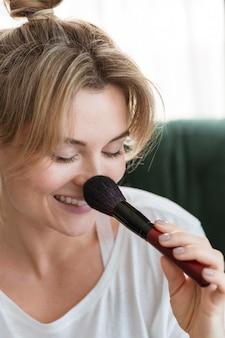 Retrato de mulher usando um pincel de maquiagem