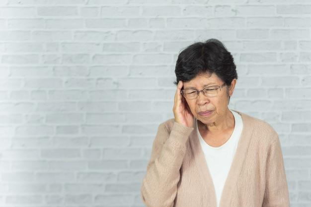 Retrato de mulher velha com dor de cabeça em cinza