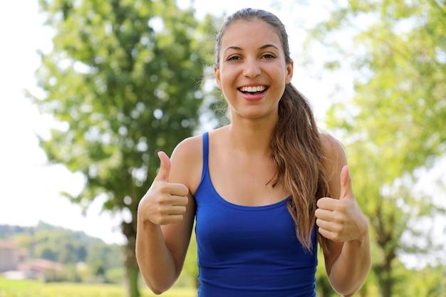 Retrato de mulher vencedora mostrando o polegar para cima