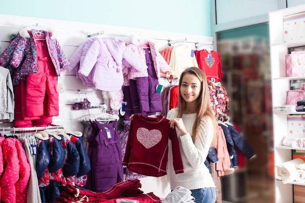 Retrato de mulher-vendedora que prepara roupas em boutique