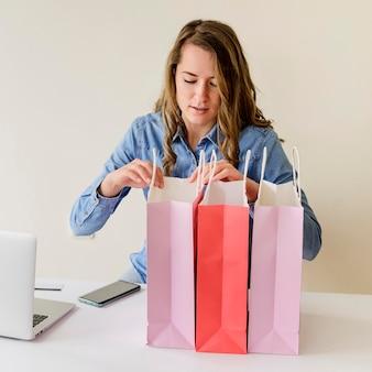 Retrato de mulher verificando sacolas de compras