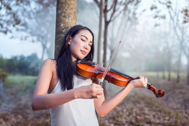 Retrato, de, mulher, vestido, em, vestido longo branco, tocando, a, violino, macio, foco, e, vindima, tom