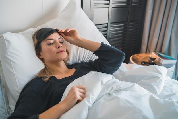 Retrato de mulher viajante relaxando e dormindo pacificamente com máscara de dormir no quarto de hotel. conceito de viagens.