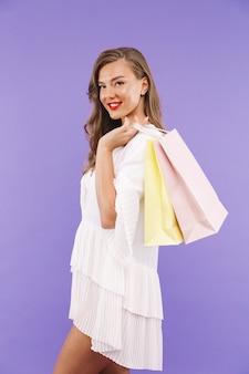 Retrato de mulher viciada em compras, vestido branco, segurando sacolas de papel com compras