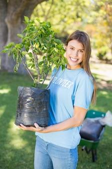 Retrato de mulher voluntária segurando a planta