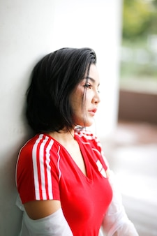 Retrato de mulheres asiáticas desviar o olhar enquanto está sentado ao ar livre.