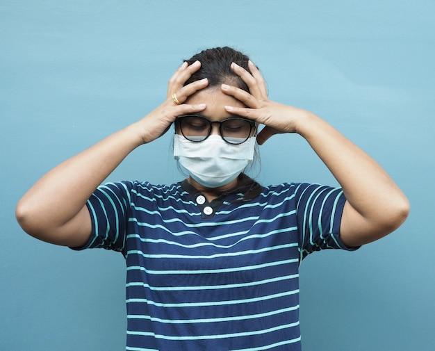 Retrato de mulheres asiáticas usando óculos e máscaras protetoras. enquanto mostra uma dor de cabeça em um fundo azul