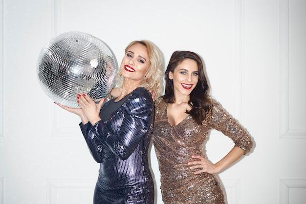 Retrato de mulheres bonitas com bola de discoteca em estúdio.