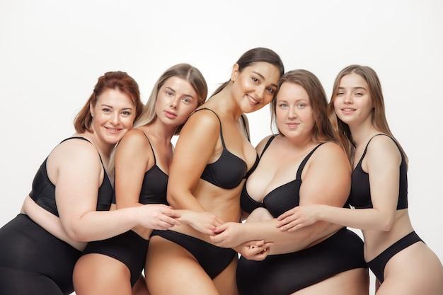 Retrato de mulheres bonitas com diferentes formas, posando em fundo branco. modelos femininos felizes. conceito de corpo positivo, beleza, moda, estilo, feminismo. diversidade.