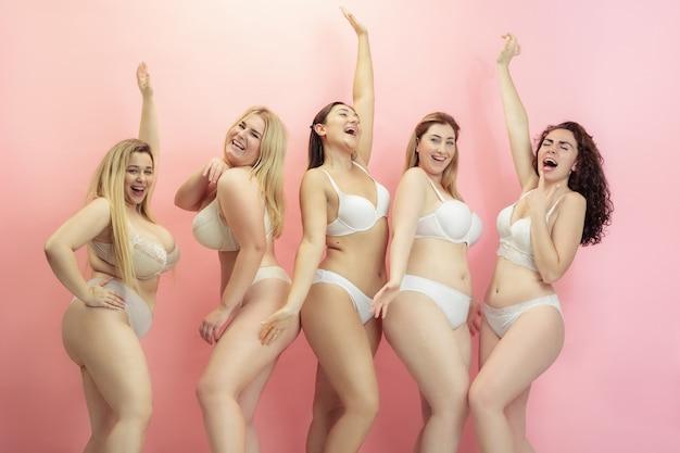 Retrato de mulheres bonitas e plus size posando em rosa