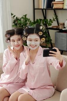Retrato de mulheres bonitas felizes e animadas com rolos de cabelo e máscaras hidratantes no rosto tomando selfie juntos