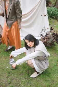 Retrato de mulheres bonitas no jardim, em pé e sentado durante o dia.