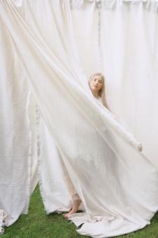 Retrato de mulheres bonitas no jardim, estando e guardando o pano no vestido branco durante o dia.