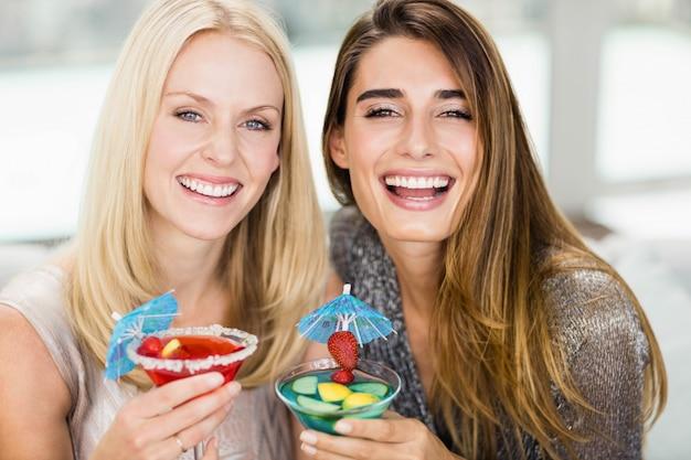Retrato, de, mulheres bonitas, sorrindo, e, tendo, mocktail