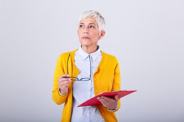 Retrato de mulheres de negócio maduro com prancheta e original à disposição com o espaço da cópia isolado na parede branca. empresária criativa pensativa, olhando para longe no escritório