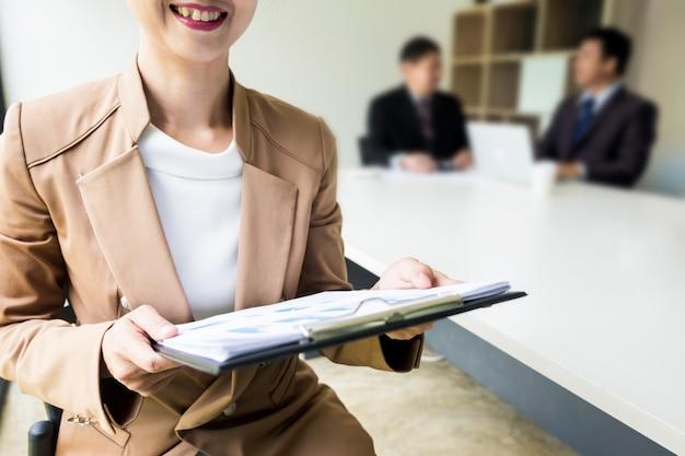 Retrato de mulheres de negócios jovens e bonitas com pessoas em segundo plano na reunião do escritório.