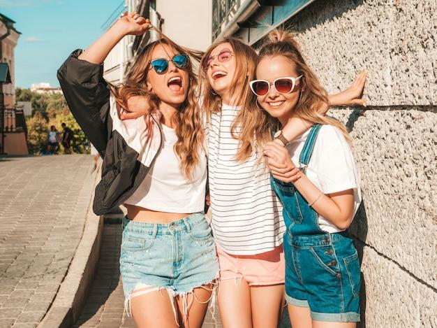 Retrato de mulheres despreocupadas sexy, posando no fundo da rua. modelos positivos se divertindo em óculos de sol.