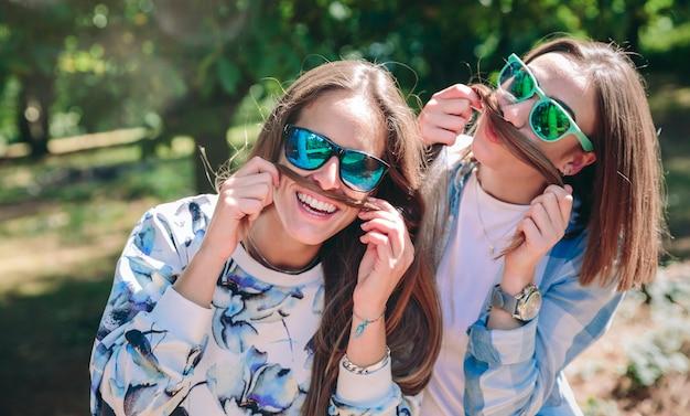 Retrato de mulheres engraçadas com óculos escuros fazendo bigodes com seus cabelos longos e rindo. conceito de relaxamento e lazer.