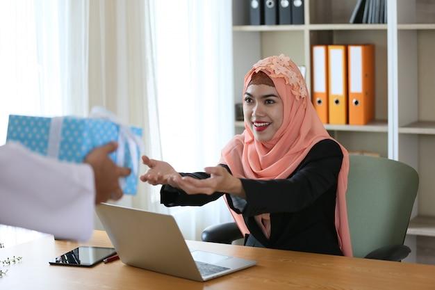 Retrato de mulheres muçulmanas recebe presente presente no escritório