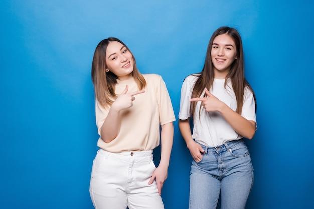 Retrato de mulheres multinacionais alegres em roupas casuais, sorrindo e apontando uma para a outra, isoladas sobre uma parede azul