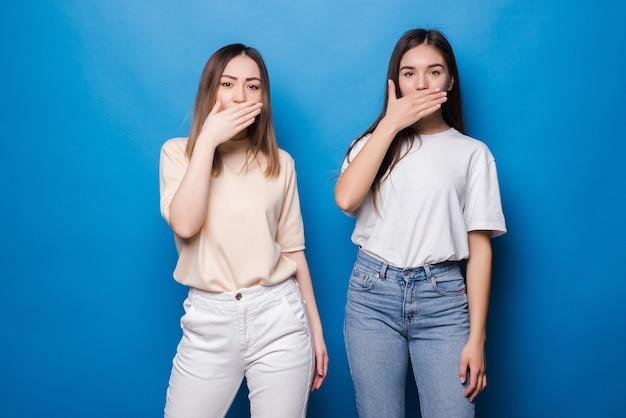 Retrato de mulheres multinacionais animadas em roupas casuais, sorrindo e cobrindo a boca, isoladas sobre uma parede azul