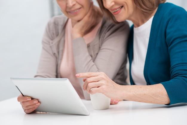 Retrato de mulheres navegando em um tablet
