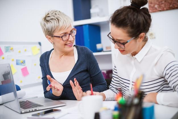 Retrato de mulheres profissionais de meia idade trabalhando juntos em projetos no escritório.