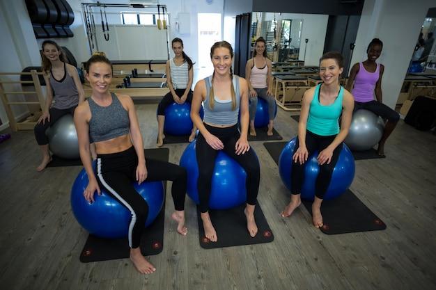 Retrato de mulheres sorridentes sentadas na bola de fitness