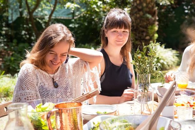 Retrato, de, mulheres sorridentes, sentando, junto, em, partido jardim