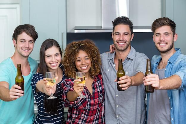 Retrato de multi étnica amigos mostrando cerveja e vinho