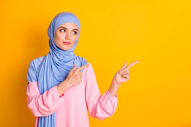 Retrato de muslimah inteligente de conteúdo atraente usando hijab demonstrando o espaço da cópia do anúncio isolado sobre o fundo de cor amarela brilhante
