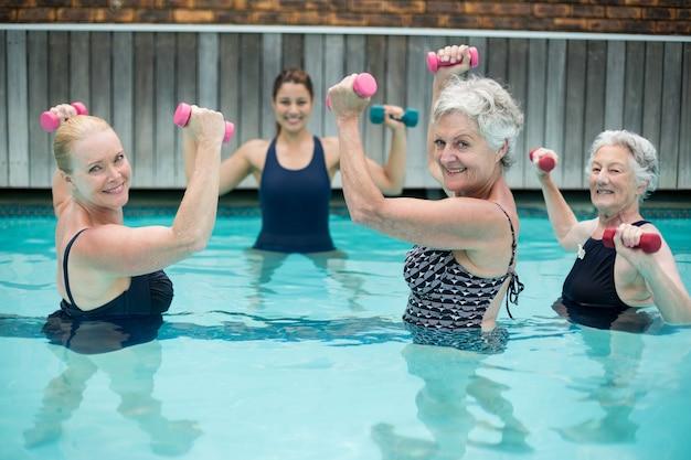 Retrato de nadadores sênior com treinador levantando halteres na piscina