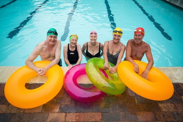 Retrato de nadadores seniores com argolas infláveis em pé à beira da piscina
