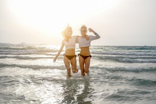 Retrato de namoradas sylish styaing no oceano de cristal ao pôr do sol
