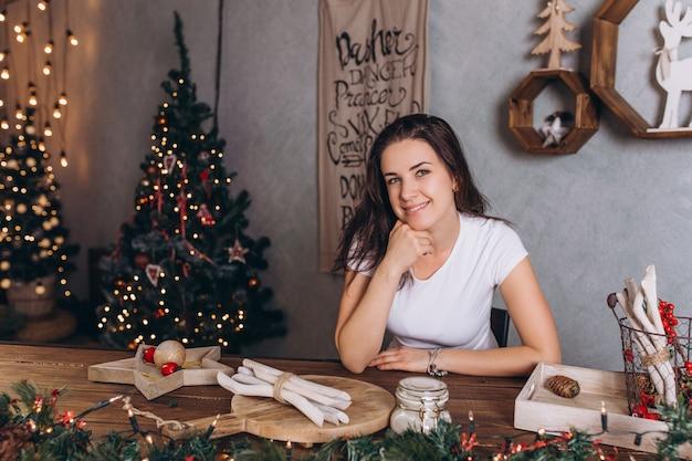 Retrato de natal da jovem mulher bonita morena em casa aconchegante