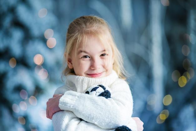 Retrato de natal da menina loira feliz criança interior estúdio, inverno nevado decorada árvore
