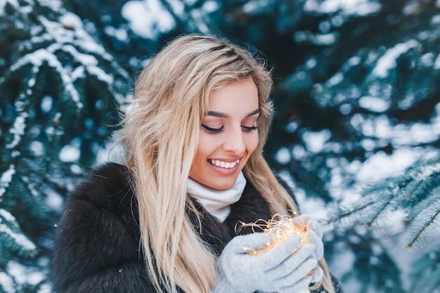 Retrato de natal de linda jovem na floresta de inverno com luzes ao ar livre