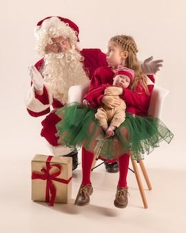 Retrato de natal de uma linda garotinha recém-nascida e de uma linda irmã adolescente vestida com roupas de natal e homem usando fantasia de papai noel e chapéu