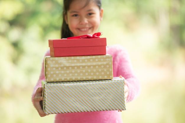 Retrato de natal de uma menina sorridente feliz com uma caixa de presente perto de um galho verde. folhas verdes bokeh fora do fundo de foco da floresta natural.