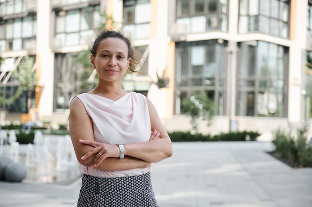 Retrato de negócios confiante de uma mulher de negócios bem-sucedida de meia-idade em traje casual, posando para a câmera com aríetes cruzados no fundo de edifícios altos. cenário urbano da cidade