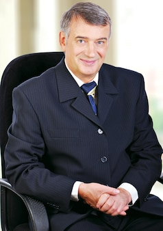 Retrato de negócios sênior de meia idade sentado na cadeira, sorrindo com as mãos postas no colo.