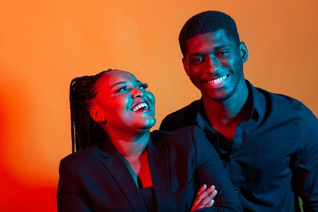 Retrato de néon escuro de jovem afro-americano e mulher. luz vermelha e azul.