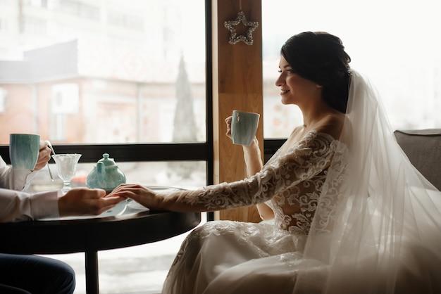 Retrato de noiva. amor, conceito de casamento. casal feliz recém-casado. noivos amorosos estão sentados em frente à janela do café, bebem chá e se entreolham